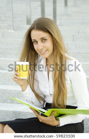 Business woman with a green folder and paper cup of coffee - stock photo