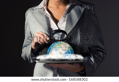 business woman with a magnifying glass looking at the planet, ecology concept - stock photo