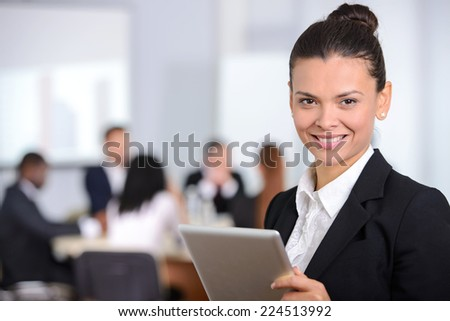 Business woman, with a tablet, people group in background at modern bright office indoors
