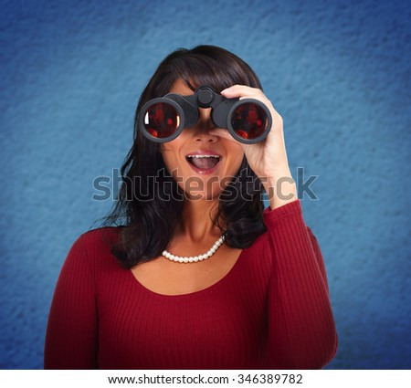 Business woman with binoculars over blue abstract background. - stock photo