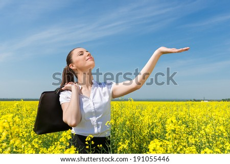 business woman with briefcase at the yellow flower field - stock photo