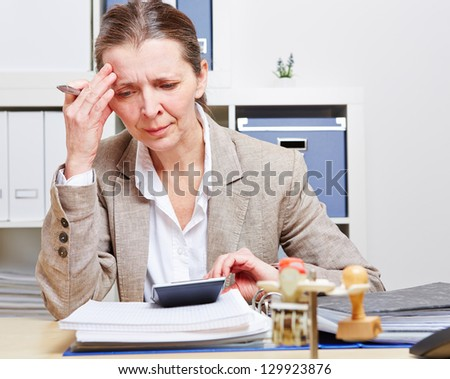 Business woman with burnout sitting in her office at the desk over files - stock photo