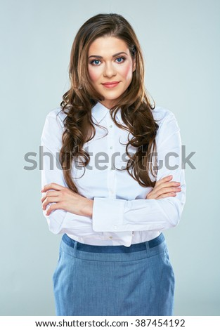 Business woman with crossed arms standing against gray background. Smiling model with long hair. - stock photo