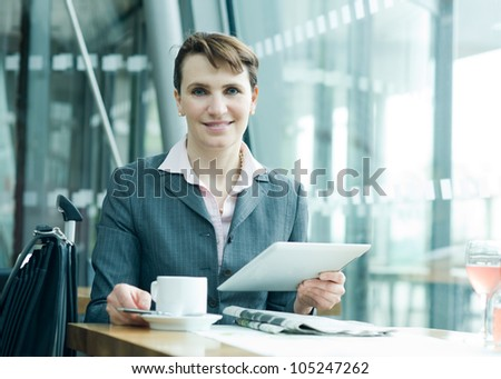 Business woman with digital tablet, luggage and news paper smiling at camera - stock photo