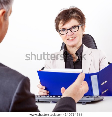 Business woman with folder speaks to man in a suit - stock photo
