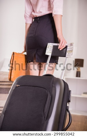 Business woman with her suitcase at the hotel room. Back view. Close-up. - stock photo