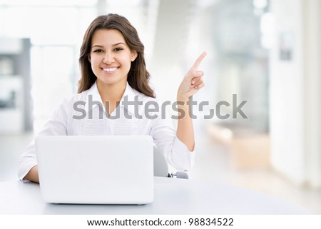 Business woman with laptop pointing to the free space