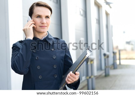 Business woman with mobile phone and file folder in front of warehouse