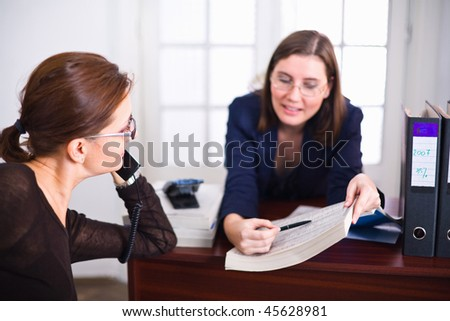 Business woman with open phonebook showing her colleague something.