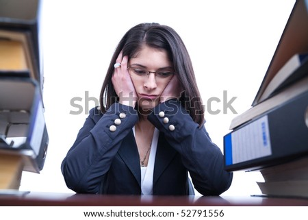 Business woman with pile of folders and binders looking overwhelmed with work after a long day - stock photo