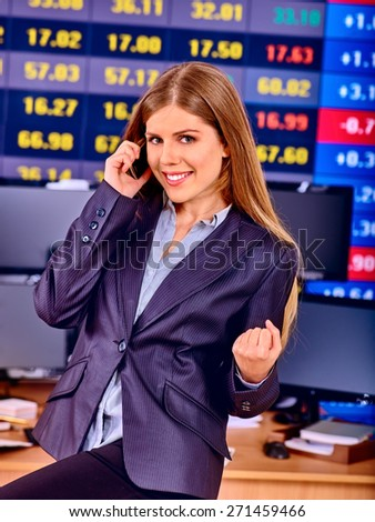 Business woman with  stock exchange board in office. Girl calls by phone.