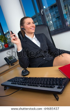 business woman with wireless headset at office desk