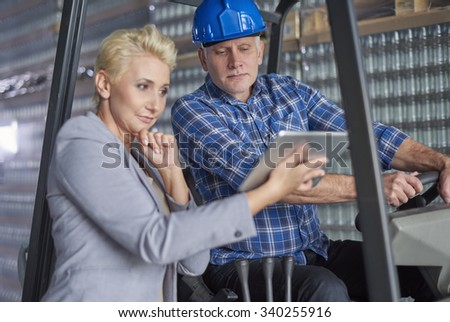 Business woman with worker in warehouse