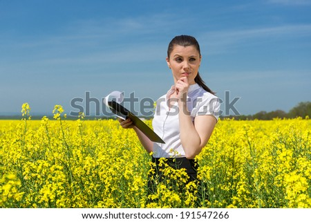 business woman with yellow flowers and file on the field - stock photo