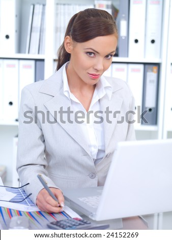 Business woman working in office, looking at camera and smiling