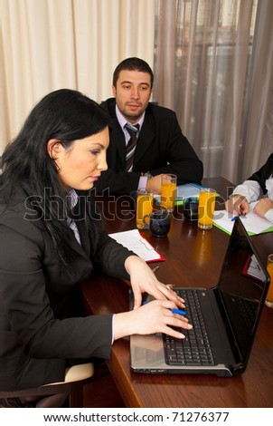 Business woman working on laptop at meeting  and other business man looking at what she typing - stock photo