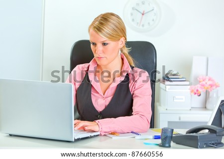 Business woman working on laptop at office desk - stock photo