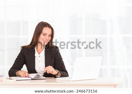 Business woman working on laptop computer at office. Modern business woman in the office with copy space. Portrait of businesswoman with laptop writes on a document at office. Office worker of laptop