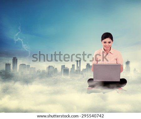 Business woman working on the cloud above the city. Cloud computing concept - stock photo