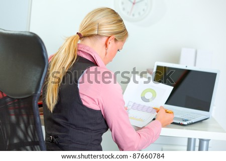 Business woman working with documents. Rear view - stock photo