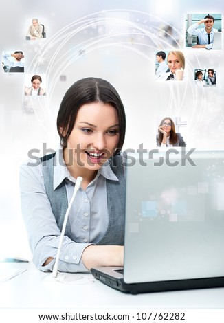 Business woman working with laptop at her office. Talking online by microphone with partners, colleagues or clients which portraits flying from the screen - stock photo