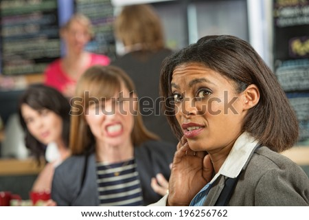 Business woman worried about angry coworker in cafeteria - stock photo