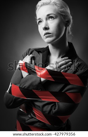 Business woman wrapped up in red tape - stock photo