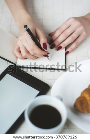 Business woman writes in a notebook