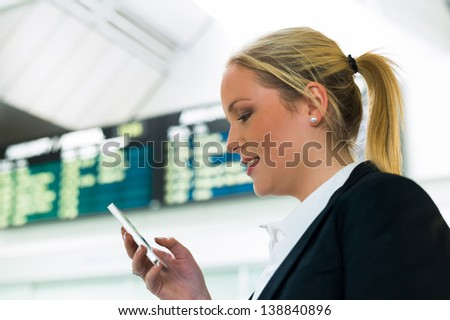 business woman writes on sms airport. roaming charges when abroad. accessibility with modern technology