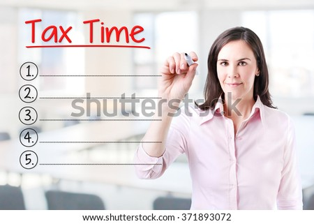 Business woman writing blank Tax Time list. Office background.  - stock photo