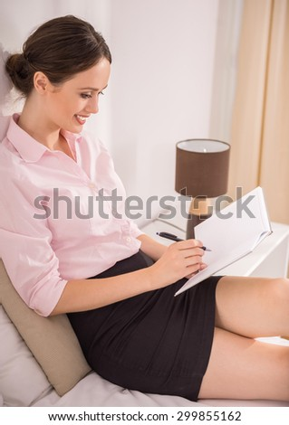 Business woman writing down her notes at notebook and smiling while sitting on bed at the hotel room. Side view.