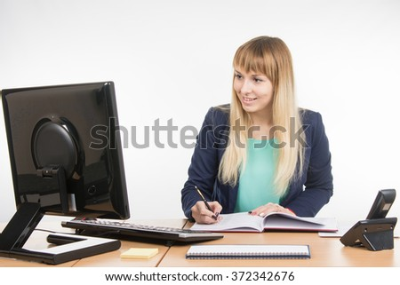 Business woman writing in a business book and looked at the computer monitor - stock photo