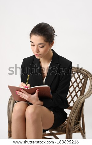 business woman writing in a notebook sitting in a wicker chair