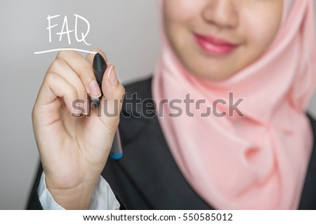 Business woman writing text : FAQ (Frequently Ask Question) over gray background