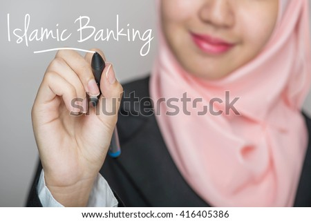 Business woman writing text : Islamic Banking over gray background
