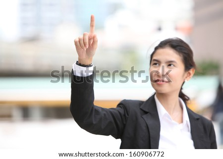 Business woman writing whatever you want with finger - stock photo