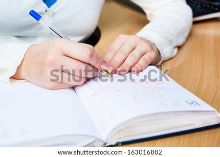 Business Woman Writing with pen in notepad - stock photo