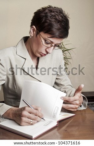Business Woman Writing with pen in notepad,close up photo