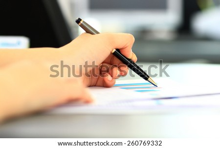 Business Woman Writing with pen in the office - stock photo