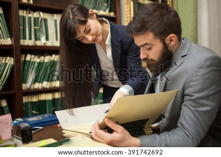 Business women and a businessman  in the attic offices  review folders with documents - stock photo