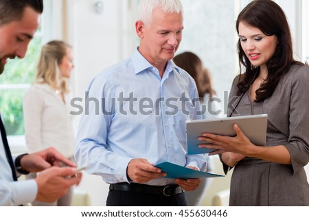 Business women and men in office looking at presentation in a standup meeting - stock photo
