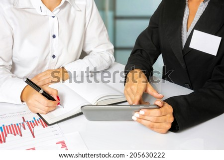 Business women doing business research, in the bright office. - stock photo