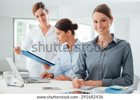 Business women team working at office desk and pointing on a report, one is smiling at camera