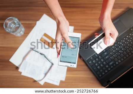 Business work place with female hands holding smart phone and bank card, top view - stock photo