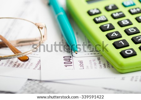 Business work station with paperwork income tax return, calculator and pen