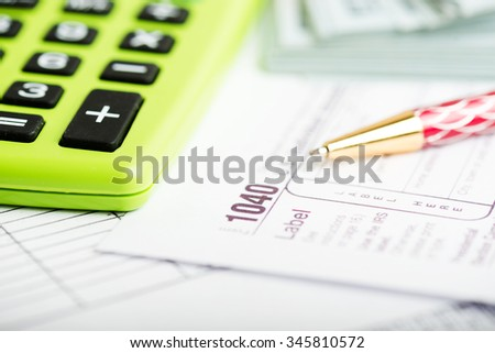 Business work station with paperwork income tax return, calculator and pen and dollar