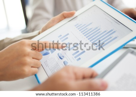 Business workers discussing digital graphs and diagrams indicating progress in work - stock photo