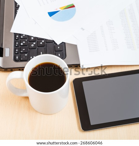 business workflow - above view mug of coffee and tablet pc on office table - stock photo