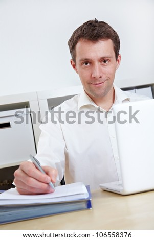 Business working with laptop and files at his desk in the office - stock photo