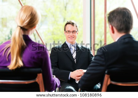 Business - young man as applicant sitting in job interview with future boss and HR - stock photo